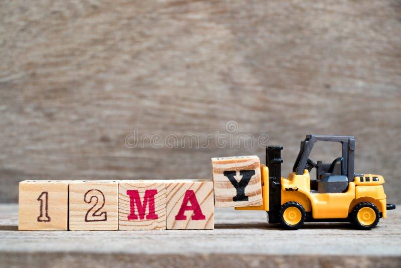 玩具铲车措辞12的举行块Y在木背景概念可以为历日的月5月 免版税图库摄影