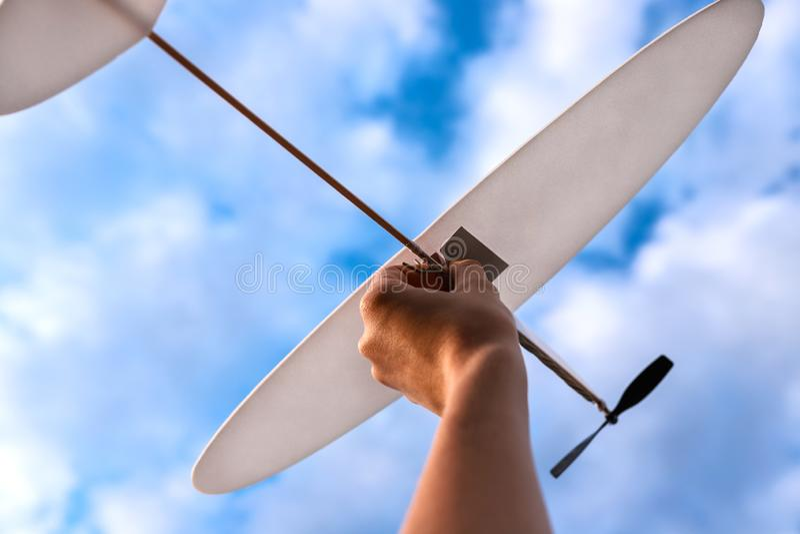 玩具飞机在天空的妇女的手上 免版税库存图片