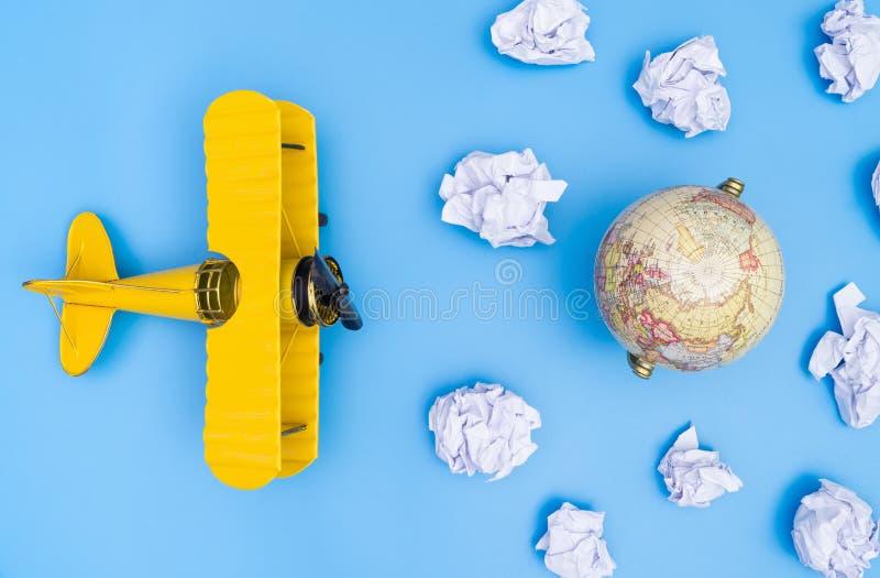 玩具飞机飞行纸云彩到世界 免版税库存照片