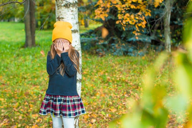 玩捉迷藏的小女孩在树附近  免版税图库摄影