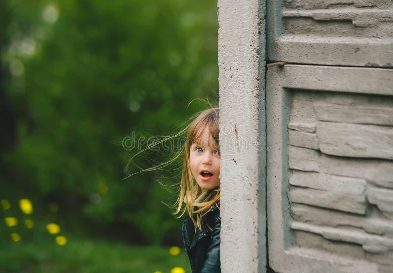 玩捉迷藏的快乐小女孩 库存照片