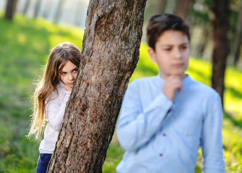 玩捉迷藏的男孩和女孩在公园 观看在男朋友的女孩 免版税库存照片