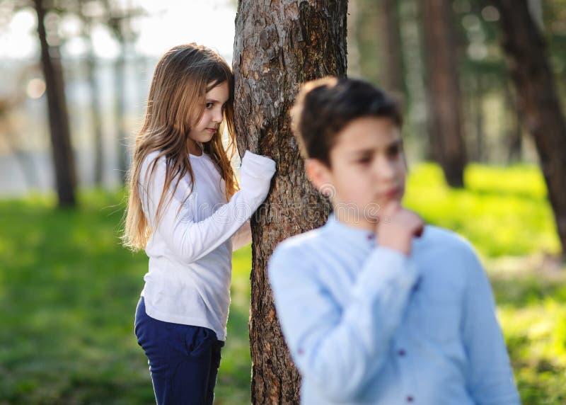 玩捉迷藏的男孩和女孩在公园 观看在男朋友的女孩 免版税图库摄影