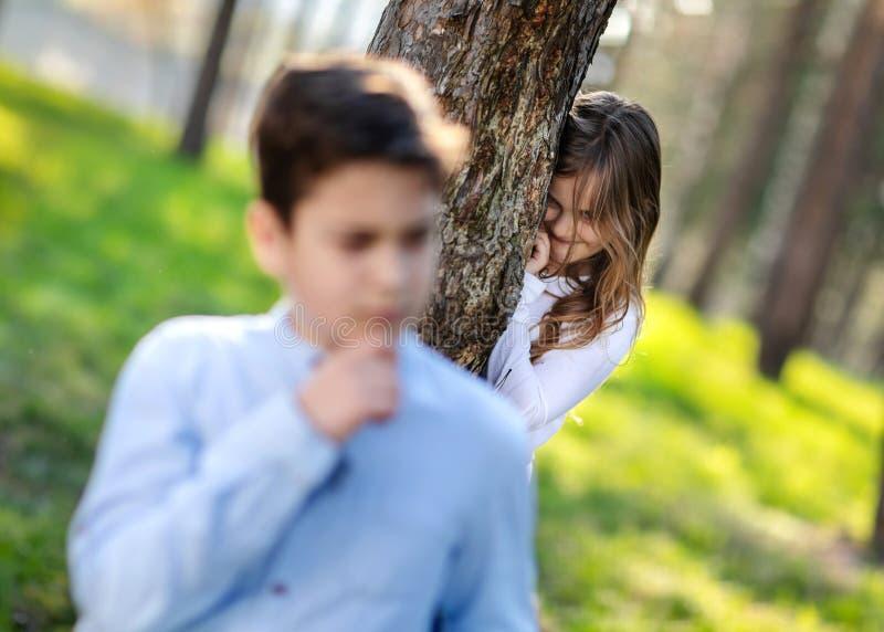 玩捉迷藏的男孩和女孩在公园 观看在男朋友的女孩 免版税库存图片