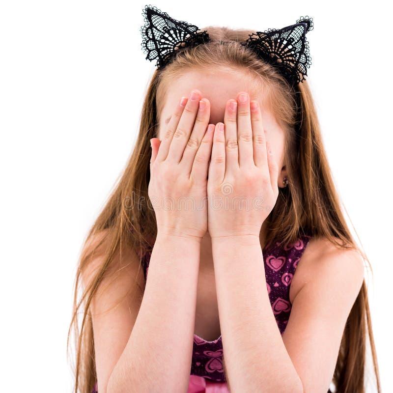 玩捉迷藏的青少年的女孩,包括她的面孔 免版税库存照片