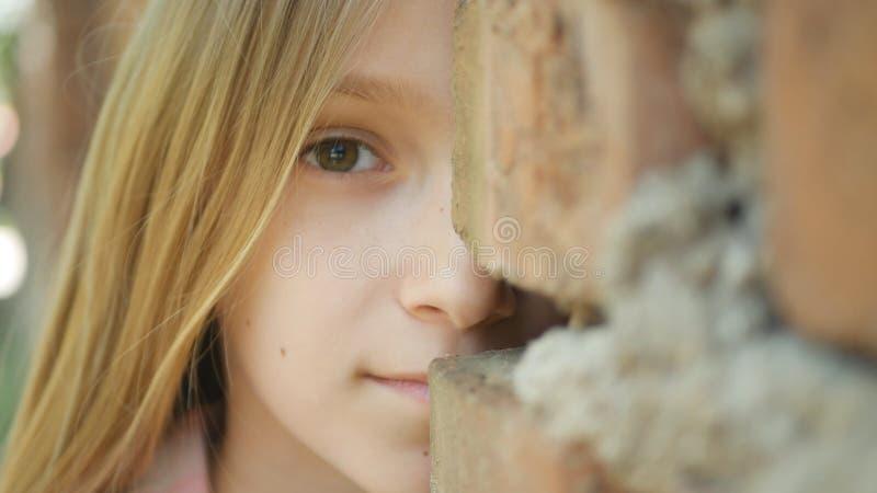 玩捉迷藏,在墙壁后的害怕的女孩的哀伤的童颜微笑秘密审议 免版税库存图片