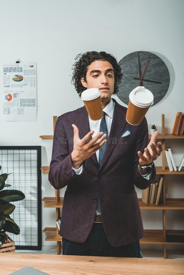 玩杂耍与一次性咖啡杯的被聚焦的商人画象  免版税库存照片