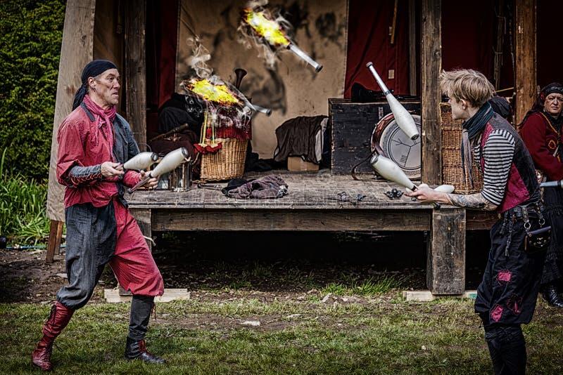 玩杂耍与在中世纪节日的火的Harlekins在城堡汉堡帽 图库摄影