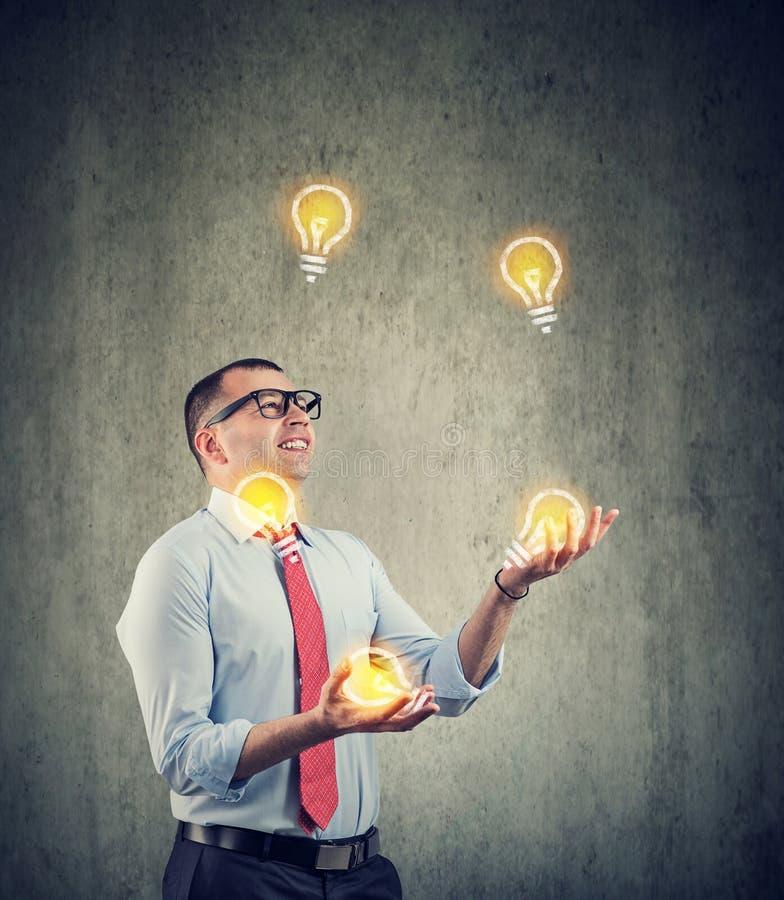 玩杂耍与新的想法电灯泡的年轻商人 免版税库存照片