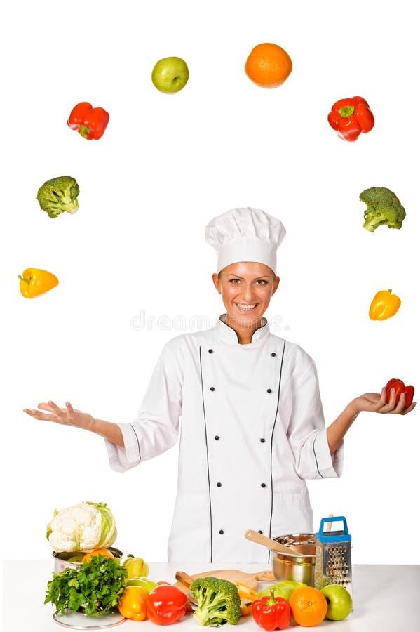 玩杂耍与新鲜蔬菜的妇女主厨。 查出 免版税库存图片