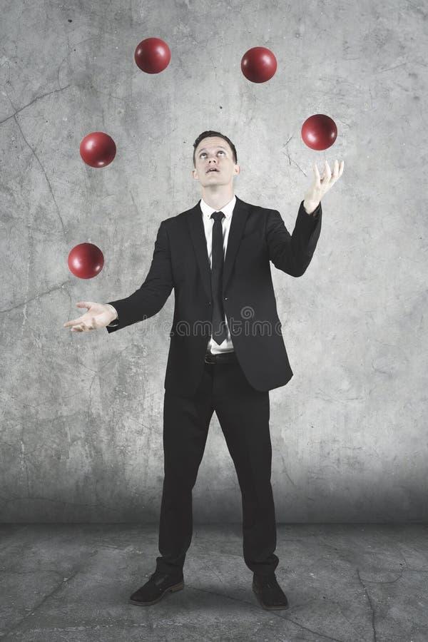 玩杂耍与红色球的美国商人 免版税库存照片