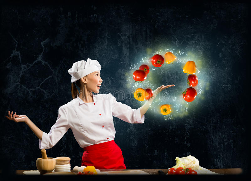 玩杂耍与菜的亚裔妇女厨师 免版税库存照片