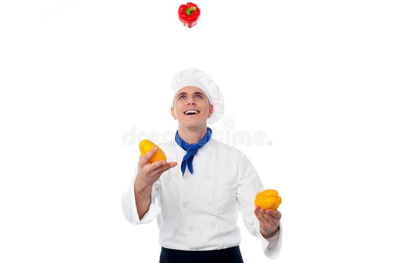 玩杂耍与菜的厨师 免版税库存图片