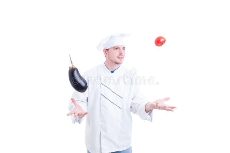 玩杂耍与菜eggpland和蕃茄的厨师或厨师 免版税库存照片