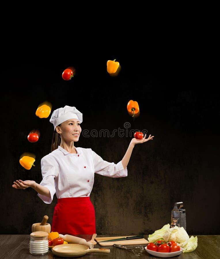 玩杂耍与蔬菜的亚裔妇女主厨 库存图片
