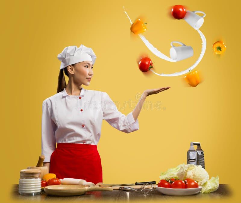 玩杂耍与蔬菜的亚裔妇女主厨 免版税库存照片
