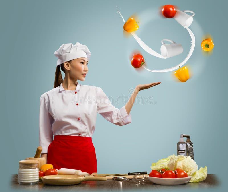 玩杂耍与蔬菜的亚裔妇女主厨 免版税图库摄影