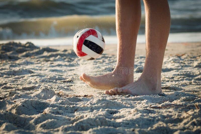 玩杂耍由海滩的一个足球 免版税库存照片