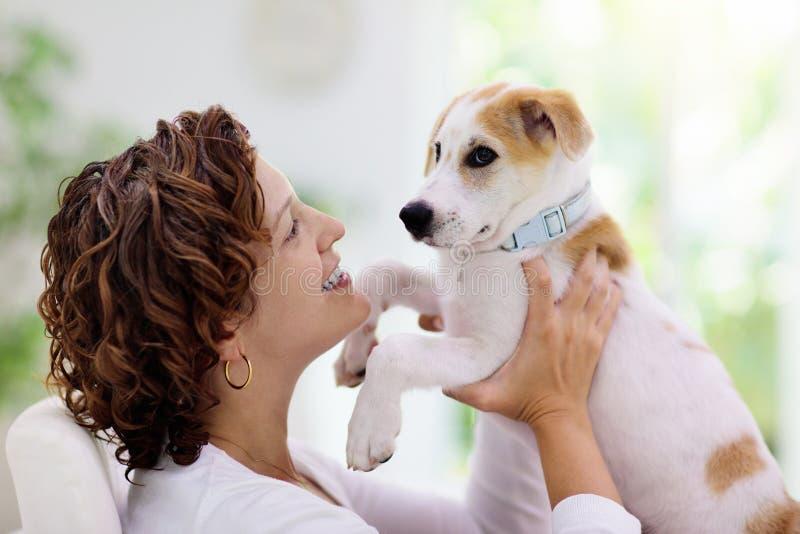 玩狗的女人 小狗和主人 免版税库存照片