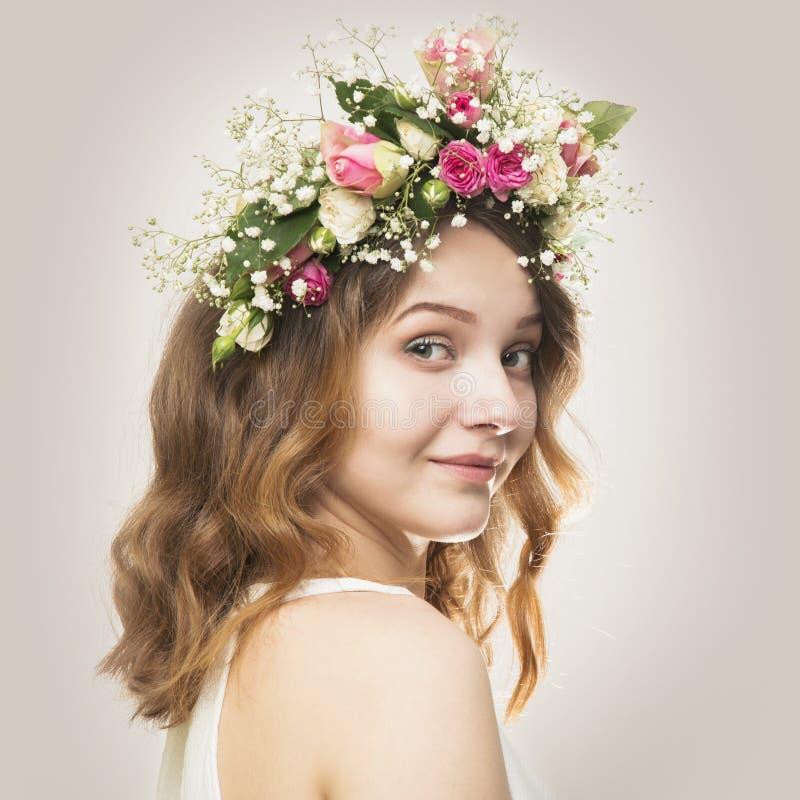 玫瑰一个花卉花圈的美丽的少妇  免版税库存照片