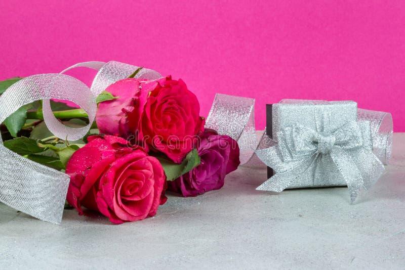 玫瑰和一个银色礼物盒庆祝的背景有丝带的 库存图片