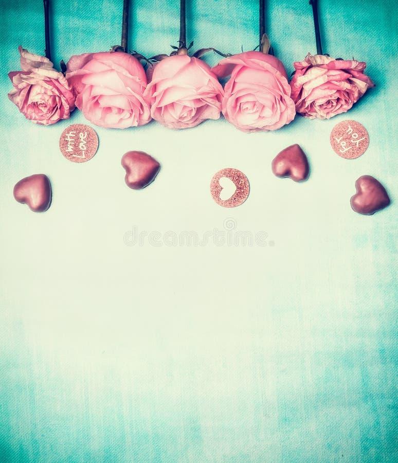 玫瑰和巧克力与文本充满爱对您蓝色绿松石背景的,减速火箭的被称呼的情人节卡片,顶视图 免版税图库摄影