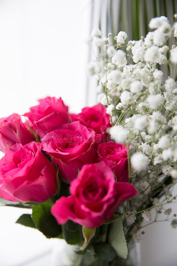 玫瑰和白花花束在一个花瓶在窗口 库存图片