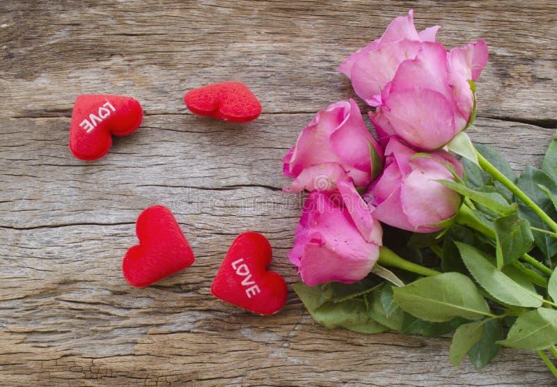 玫瑰和红色心脏在老木板,情人节b把枕在 免版税库存照片