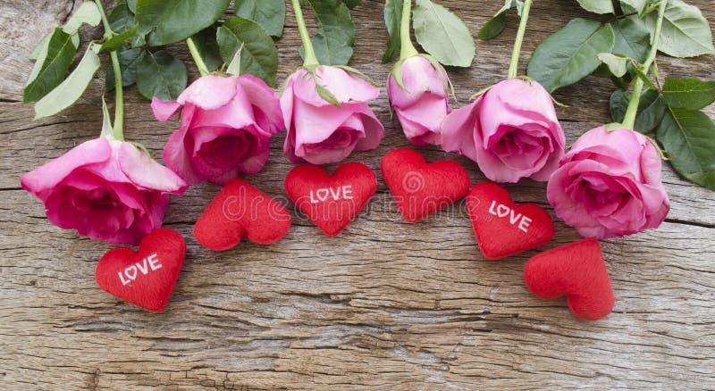 玫瑰和红色心脏在老木板,情人节b把枕在 免版税库存图片