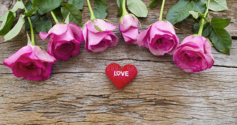 玫瑰和红色心脏在老木板,情人节b把枕在 库存照片