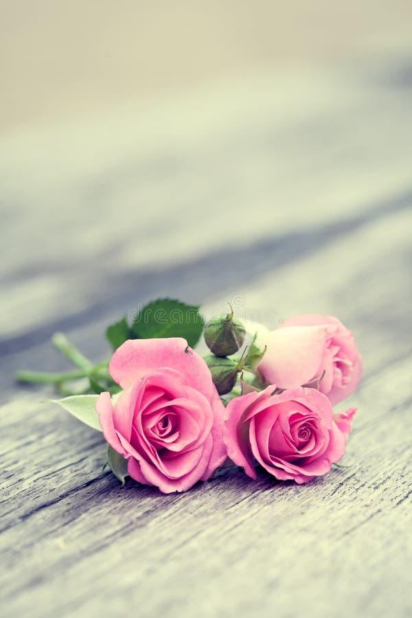 玫瑰在老木背景捆成一束 库存照片