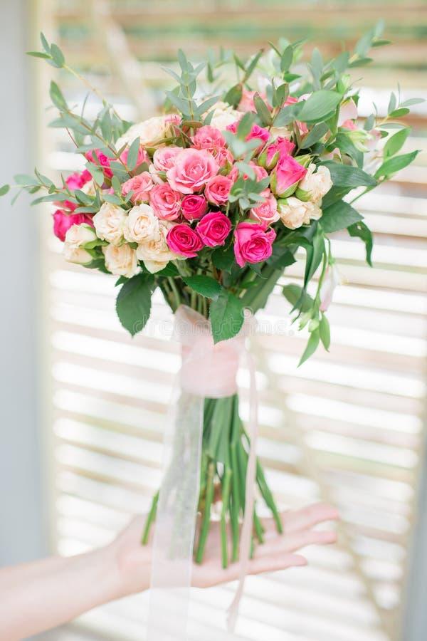 玫瑰婚礼花束在新娘的手上 免版税库存图片
