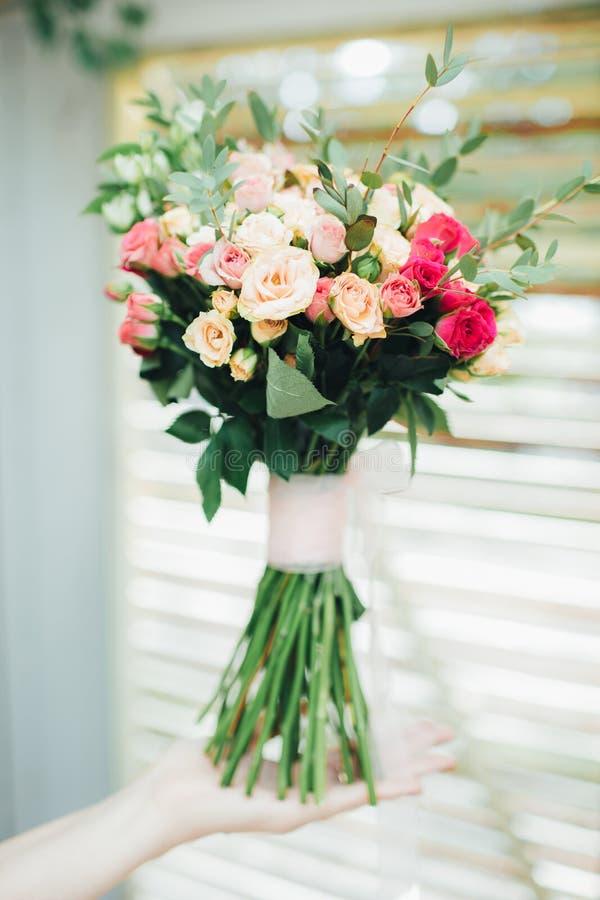 玫瑰婚礼花束在新娘的手上 免版税库存照片