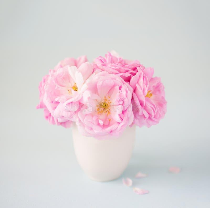 玫瑰小浅粉红色的花束在Ñ  eramic花瓶的反对苍白灰色背景 免版税库存照片