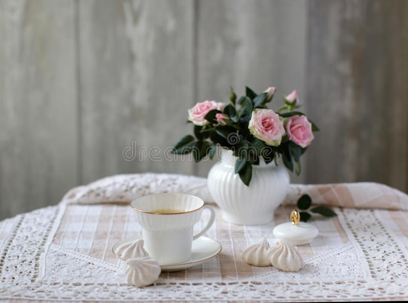 玫瑰秀丽花束在白色瓷糖罐,瓷茶杯,葡萄酒样式,花卉场面的 免版税图库摄影