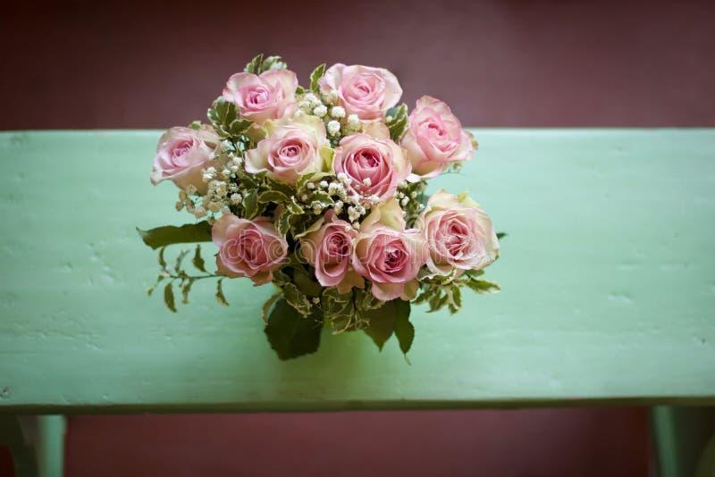 玫瑰精美花束在一条破旧的别致的长凳的 库存图片