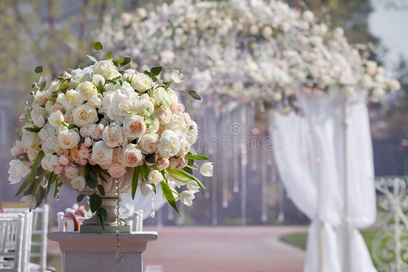玫瑰美丽的花束在一个花瓶的在婚礼曲拱的背景 婚礼的美好的设定 免版税库存照片