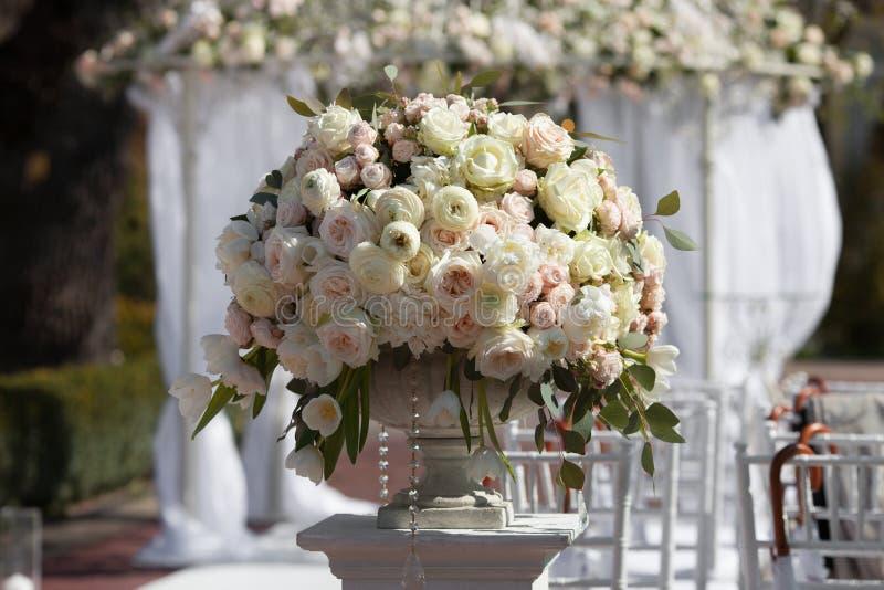 玫瑰美丽的花束在一个花瓶的在婚礼曲拱的背景 婚礼的美好的设定 图库摄影