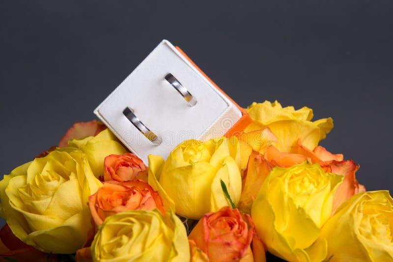 玫瑰色花和婚戒花束在箱子在灰色 库存图片