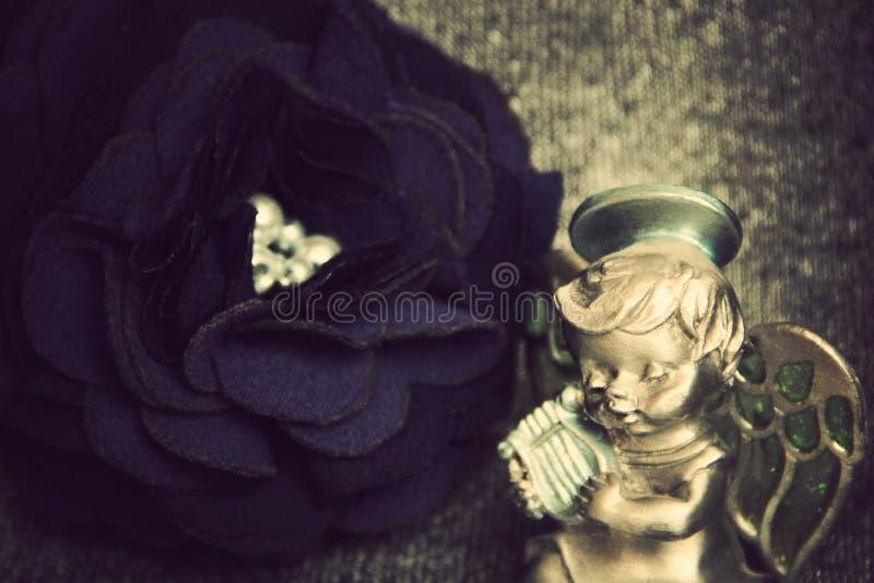 一朵人为玫瑰由布料制成和使用的天使在里拉琴 一张照片 葡萄酒 照片图片