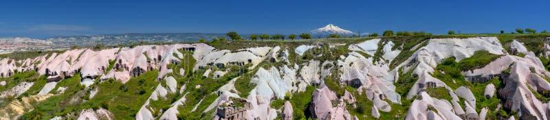 玫瑰色谷全景与登上Erciyes,格雷梅国立公园峰顶的在卡帕多细亚土耳其 免版税图库摄影