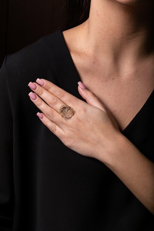 玫瑰色金子妇女圆环以壳的形式与石头珍珠在手指的,在黑背景 免版税库存照片