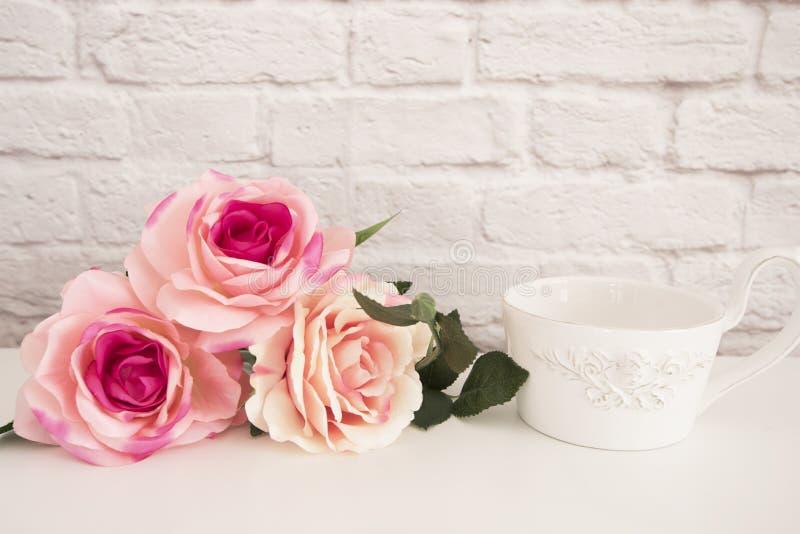 玫瑰花束在一张白色书桌, A上的大咖啡在前面天使,浪漫花卉框架背景,花卉被称呼的墙壁嘲笑的 免版税库存照片