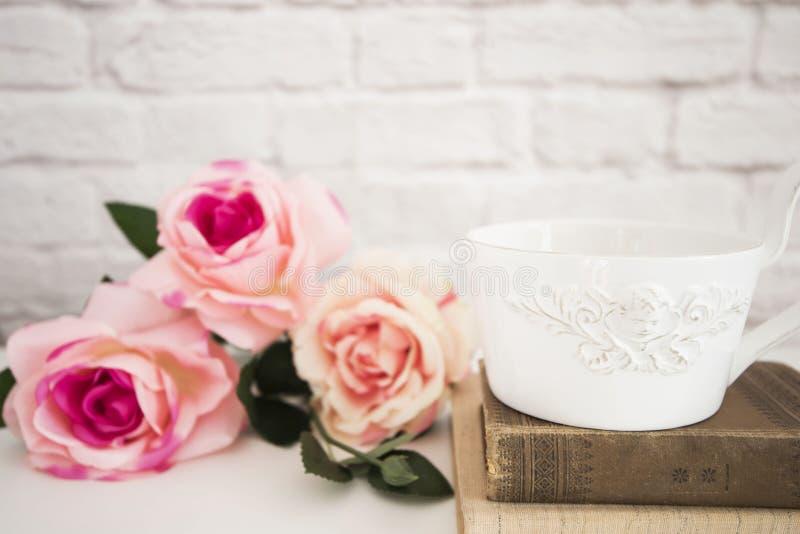 玫瑰花束在一张白色书桌, A上的大咖啡在旧书的,浪漫花卉框架背景,花卉被称呼的墙壁嘲笑 图库摄影