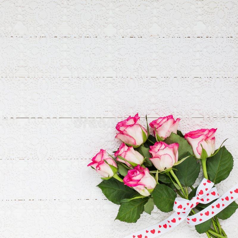 玫瑰花束在白色钩针编织桌布的 顶视图 免版税图库摄影