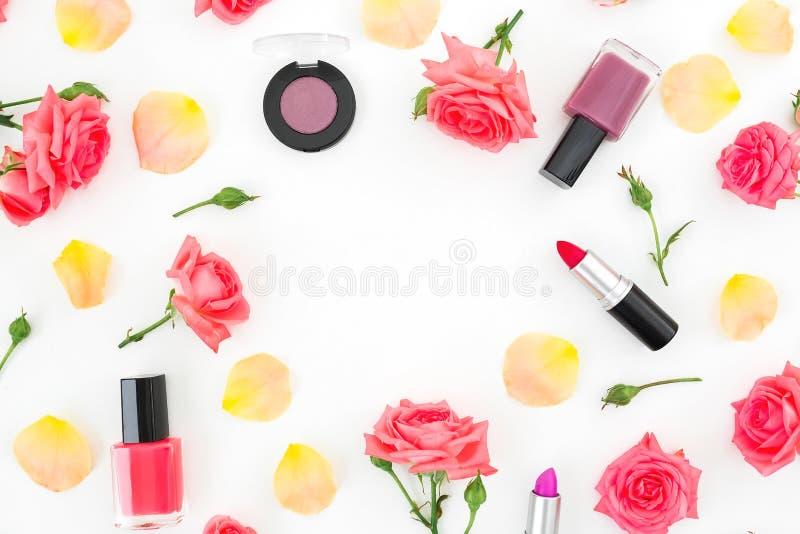 玫瑰花花框架,瓣和女性在白色背景组成化妆用品 平的位置,顶视图 图库摄影
