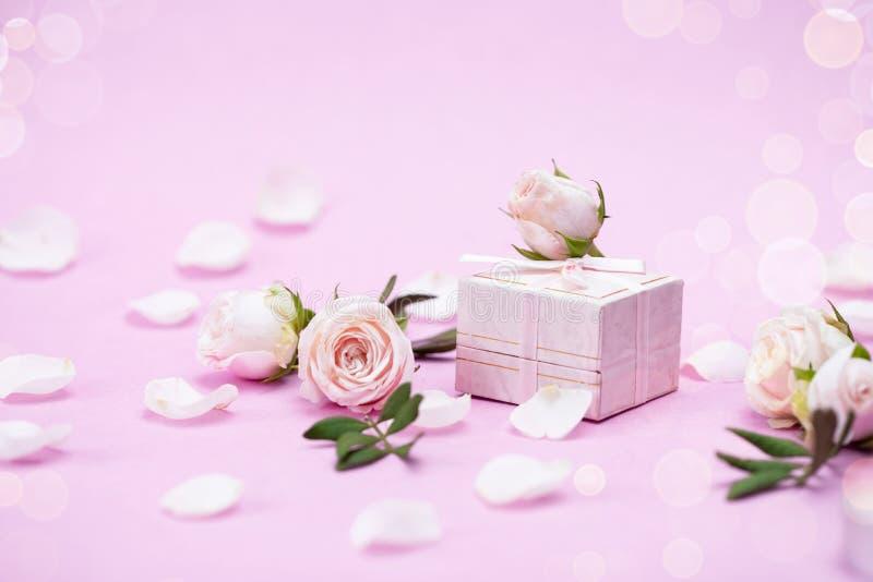 玫瑰花蕾,瓣,在桃红色背景的礼物盒 一张贺卡的概念 婚礼,情人节,生日 库存图片