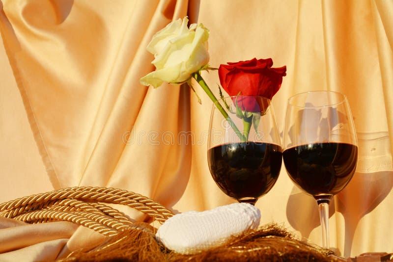 玫瑰,心脏,杯在金黄背景的红葡萄酒 免版税库存图片