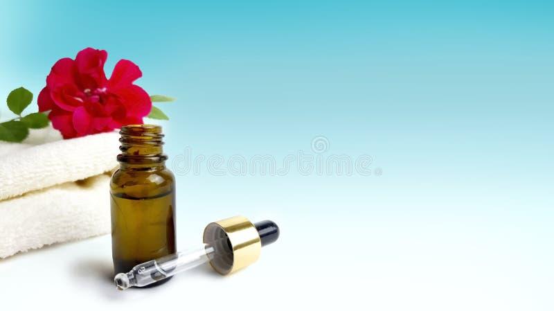玫瑰,毛巾,在深蓝蓝色背景的精油瓶 免版税库存图片