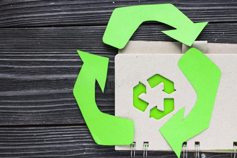 环保,生态和回收概念,回收标志、笔记薄和垃圾在黑暗的木背景 免版税图库摄影